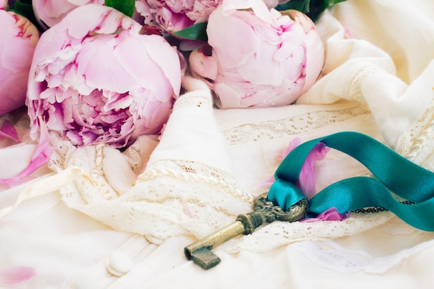 Ключ с цветами пиона на винтажной кружевной одежде