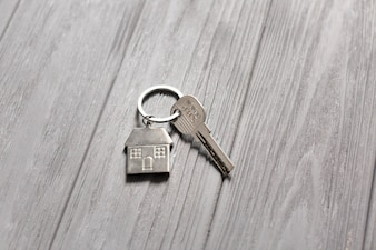 Key with small house on wooden table