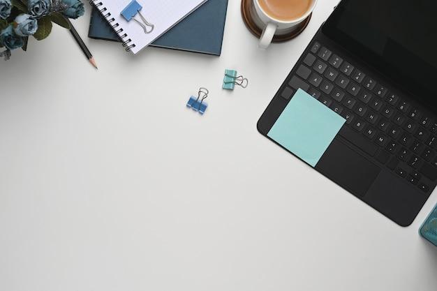 키보드와 화이트 책상에 노트북 종이 커피.