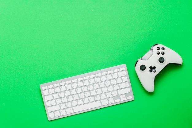 キーボードと緑の背景のゲームパッド。コンソール上のゲーム、オンラインゲームのコンセプト。フラット横たわっていた、トップビュー。