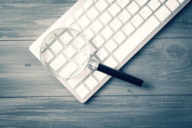 키보드 및 돋보기. 회색 나무 테이블에 검색 개념