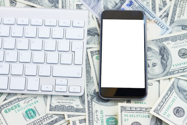 Клавиатура и современный телефон на денежном столе