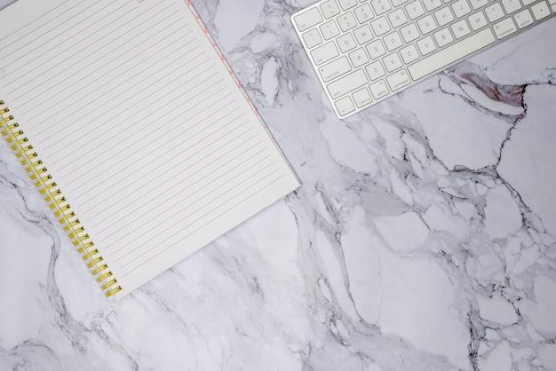 Клавиатура и ноутбук на мраморной поверхности