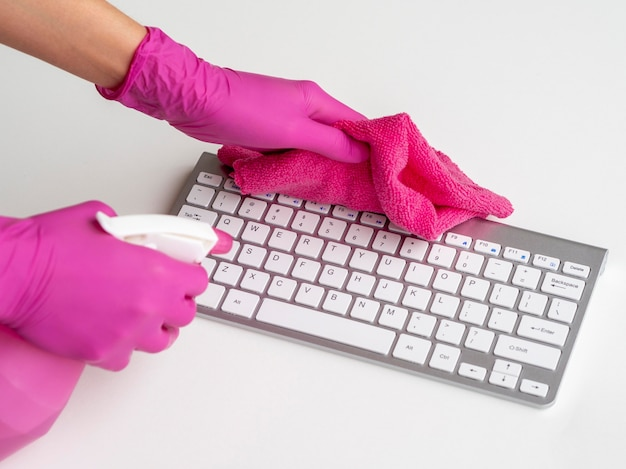 Keyboard being disinfected by person with surgical gloves