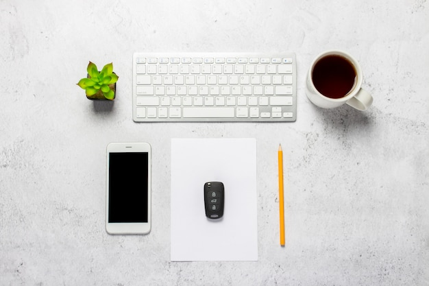 Keyboard, blank paper, pencil, phone, car keys, cup with coffee and a flower indoor on a concrete background.