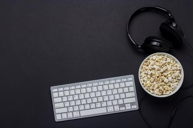 Клавиатура, чаша с попкорном и наушники на черном фоне. концепция игры на пк, игры, просмотр фильмов, телешоу, спортивные соревнования на пк. плоская планировка, вид сверху.