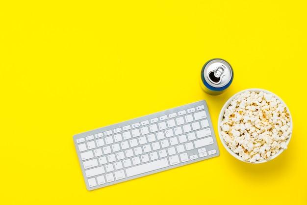 Клавиатура, банка напитка и миску попкорна на желтом фоне. концепция просмотра фильмов, сериалов, шоу, спортивных онлайн. плоская планировка, вид сверху
