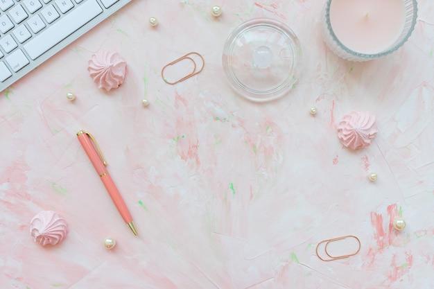 キーボード、クリップ、キャンドル、ピンクの机の上のペン