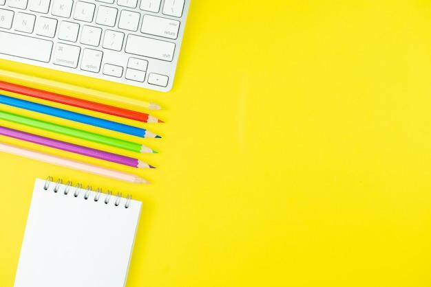 キーボード、カラフルなpensilsと黄色の背景にメモ帳プランナー