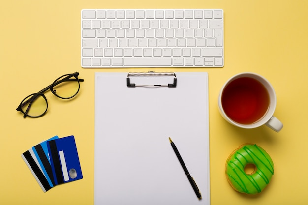 Keyboard, cup of tea, credit cards, paper and pen on yellow background.