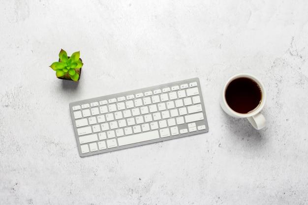 Клавиатура, чашка с кофе и цветок в помещении на конкретной предпосылке.