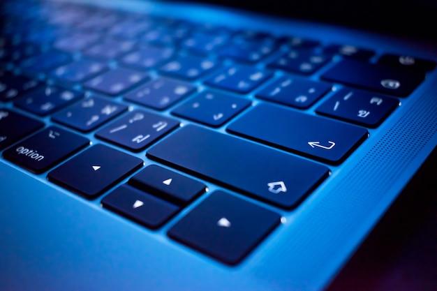 Keyboard in dark room, close up button enter.