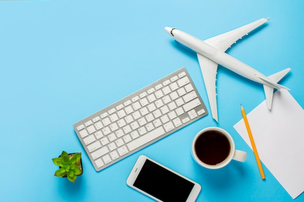 Keyboard, flower, airplane, cup with tea or coffee, a blank sheet and a pencil on a blue