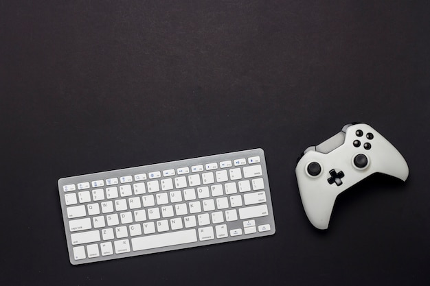 Keyboard and gamepad on a black background. the concept of the game on the pc, gaming, console. flat lay, top view.