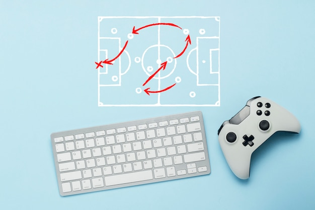 Keyboard and gamepad on a blue background. doodle drawing with tactics of the game. football. the concept of computer games, entertainment, gaming, leisure. flat lay, top view.