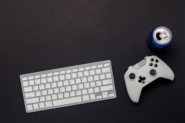 Keyboard, gamepad and a can of drink on a black background. the concept of the game on the pc, gaming, console. flat lay, top view.