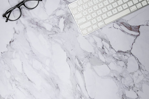 Keyboard and glasses on marble surface