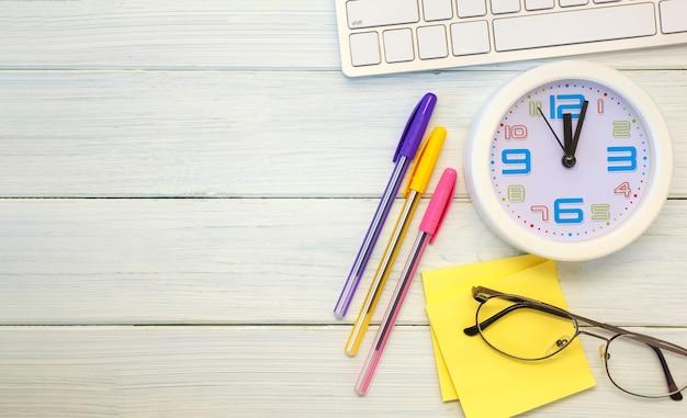 オフィスデスクとして白い木製の背景にキーボード、メガネ、ペン、時計