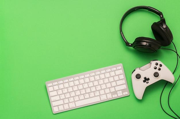 キーボード、ヘッドフォン、緑の背景のゲームパッド。コンソール上のゲーム、オンラインゲームのコンセプト。フラット横たわっていた、トップビュー。