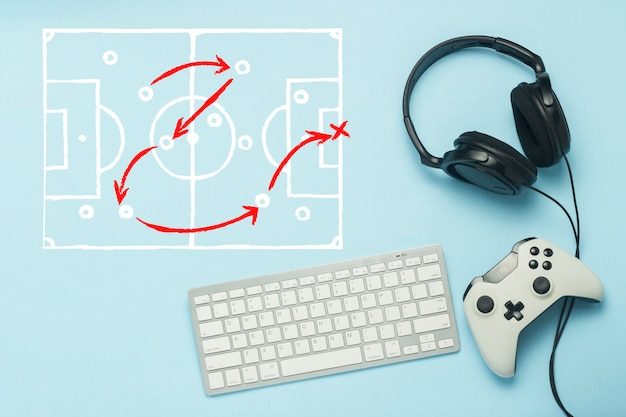 Keyboard, headphones and gamepad on a blue background. added drawing with the tactics of the game. football. the concept of computer games, entertainment, gaming, leisure. flat lay, top view.