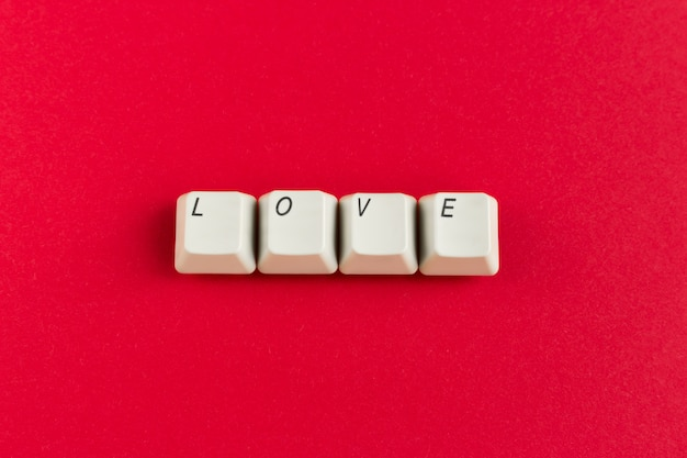 Keyboard keys with love word written using white buttons on red background.