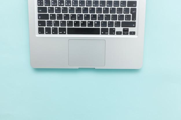 Keyboard laptop computer isolated on blue pastel desk background. modern information technology and sofware advances. freelance home office programmer or designer workspace concept