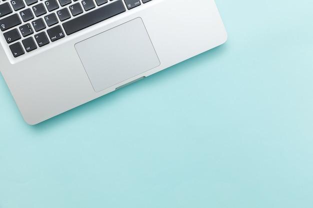 블루 파스텔 책상 배경에 고립 된 키보드 노트북 컴퓨터. 최신 정보 기술 및 소프트웨어 발전. 프리랜서 홈 오피스 프로그래머 또는 디자이너 작업 공간 개념
