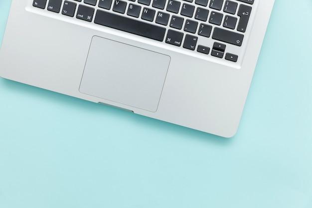 파란색 파스텔 책상 배경에 분리된 키보드 노트북 컴퓨터입니다. 현대 정보 기술과 소프트웨어가 발전합니다. 프리랜서 홈 오피스 프로그래머 또는 디자이너 작업 공간 개념