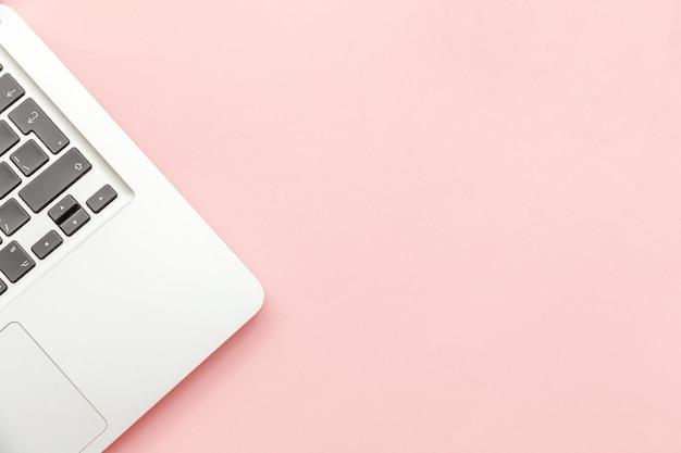 핑크 파스텔 책상 배경에 고립 된 키보드 노트북 컴퓨터. 최신 정보 기술 및 소프트웨어 발전. 프리랜서 홈 오피스 프로그래머 또는 디자이너 작업 공간 개념