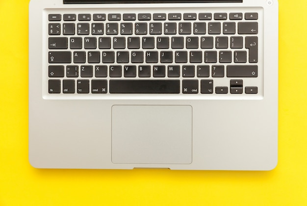 노란색 책상 배경에 고립 된 키보드 노트북 컴퓨터입니다. 최신 정보 기술 및 소프트웨어 발전. 프리랜서 홈 오피스 프로그래머 또는 디자이너 작업 공간 개념