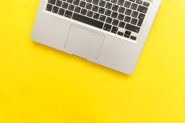 노란색 책상 배경에 분리된 키보드 노트북 컴퓨터입니다. 현대 정보 기술과 소프트웨어가 발전합니다. 프리랜서 홈 오피스 프로그래머 또는 디자이너 작업 공간 개념