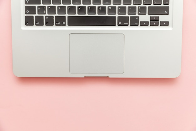 Keyboard laptop computer isolated on pink pastel desk background. modern information technology and sofware advances. freelance home office programmer or designer workspace concept