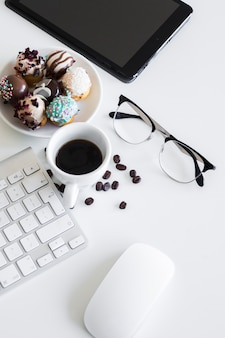 Keyboard near cup, tablet, eyeglasses, computer mouse andcookies on plate