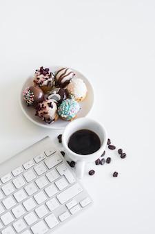 Keyboard near mug and biscuits on plate