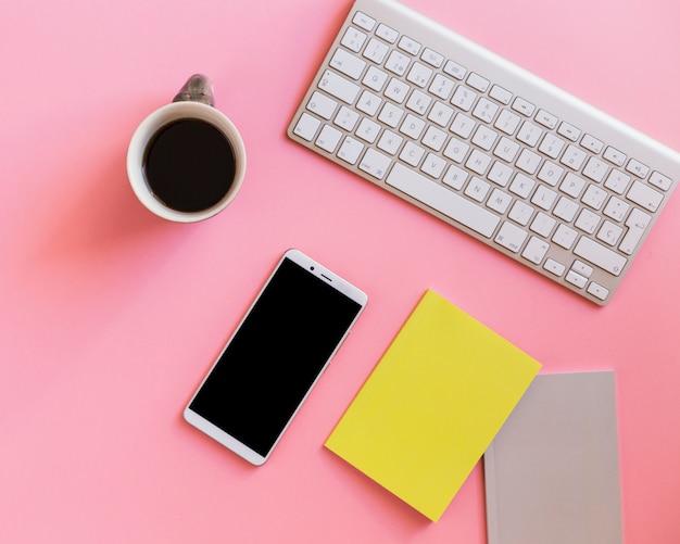 Клавиатура возле набора документов, чашка и смартфон