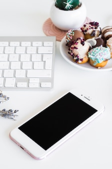 Keyboard near smartphone and cookies on plate