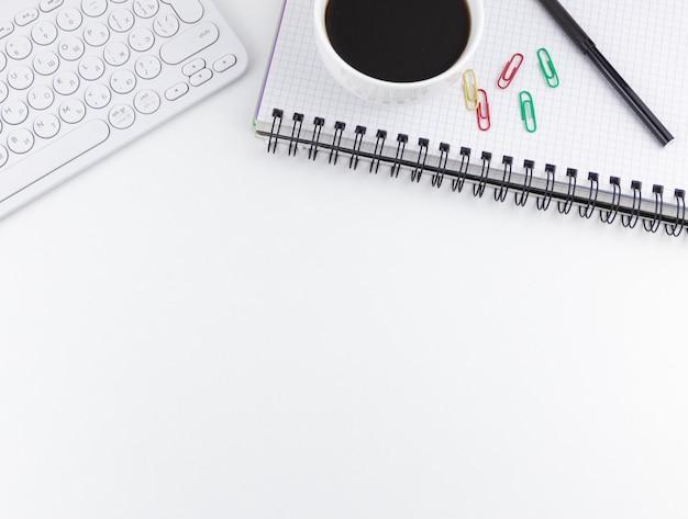 Клавиатура ноутбука и чашка кофе на белом фоне