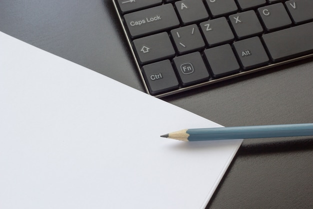 Keyboard, notebook and pencil on the table, top view
