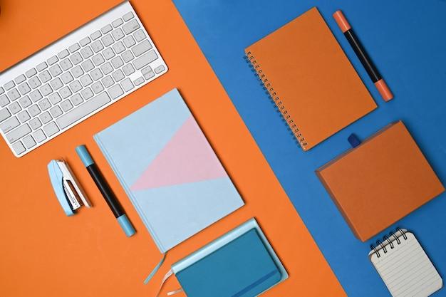 青とオレンジの2トーンの背景にキーボード、ノートブック、文房具。