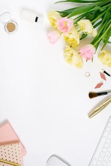 Клавиатура на белом фоне с цветами тюльпана, блокнотов, косметики, украшений и аксессуаров flat lay. вид сверху. концепция офиса женщины-фрилансера.
