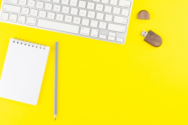 Keyboard, pencil, usb flash and notepad planner on yellow background.