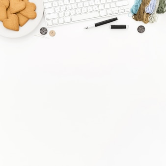 A keyboard, a plate of cookies, some thread, and buttons on a white surface