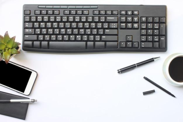 화이트 책상에 키보드, 스마트 폰, 노트북, 컵 커피, 펜 및 용품 장소.
