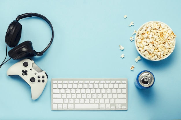 Keyboard and tin can with a drink, energy drink, a bowl of popcorn, a gamepad and headphones on a blue background. the concept of computer games, entertainment, gaming, leisure. flat lay, top view