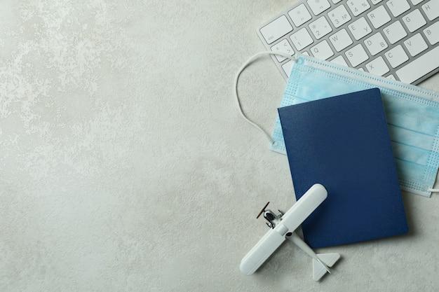 白いテクスチャ背景にキーボード、おもちゃの飛行機、パスポート、医療マスク