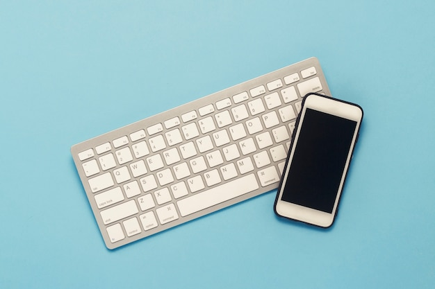 Keyboard and white mobile phone on a blue background. business concept, office work, mobile app and website. flat lay, top view