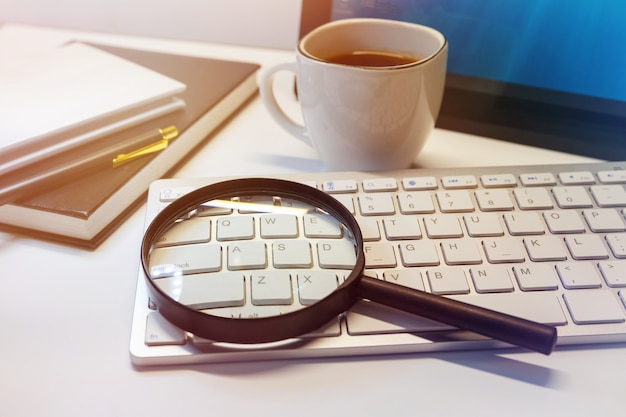 Keyboard with a magnifying glass and a cup of coffee on a desk