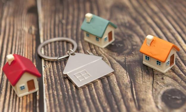 木製の背景にキーチェーンとおもちゃの家。