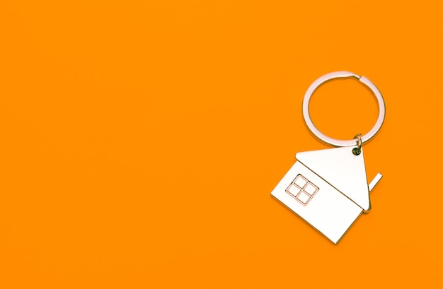 Keychain in the form of a house on a orange background