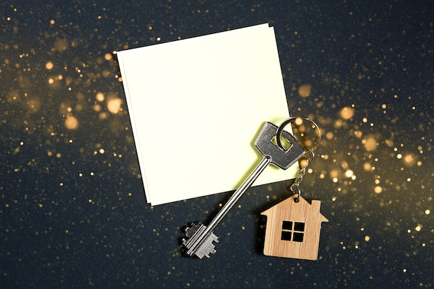 Keychain in the shape of house with key on a black background with a square sheet for notes.